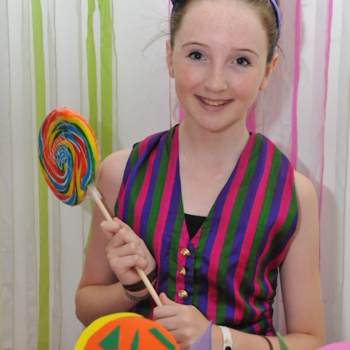 girl smiling and holding lollipop
